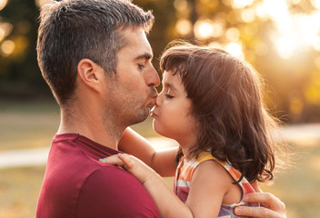 Portrait of father holding daughter in his hands hugging each other outdoors, he kissing her on nose.