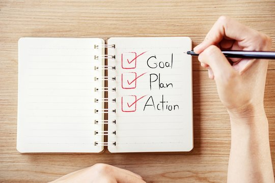 woman hand writing text goal plan action and checklist on notebook