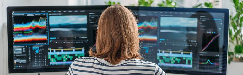 panoramic shot of editor working near computer monitors