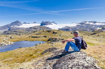 Male enjoying view on Krossbu glacier Smorstabbrean from Sognefjellshytta, National scenic route Sognefjellet in Sogn og Fjordane in Western Norway