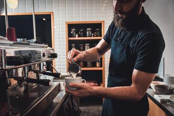 Fototapeta Barista preparing cappuccino on espresso machine for customer in coffee shop. obraz