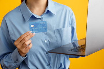 Closeup picture of laptop and shopping credit card in woman's hands