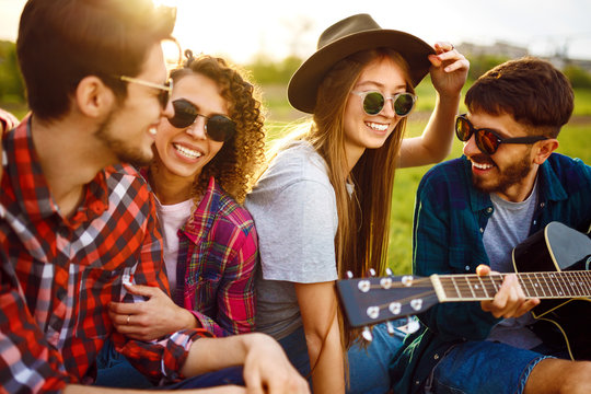 Group of happy friends with guitar having fun spending free time together in park sitting on grass. The guy plays the guitar. Young people enjoying party in the summer park. Rest, fun, summer concept.