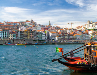 Portugal, Porto, colored houses of old town in Porto, colorful boats on Douro river, Porto by river, Porto old town view, red wooden boats on the river, portuguese flag on karma boat