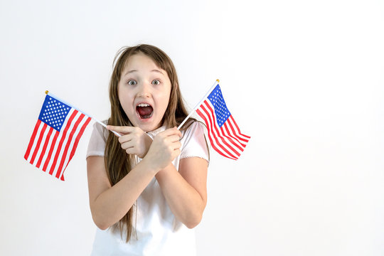 Teenager girl with two american flags in hand on a white background. The concept of education in the United States. Emotions of surprise and delight on the face of the child