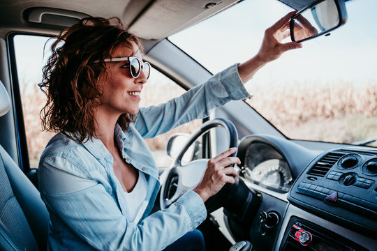 young beautiful woman driving a car and adjusting rear mirror. travel concept