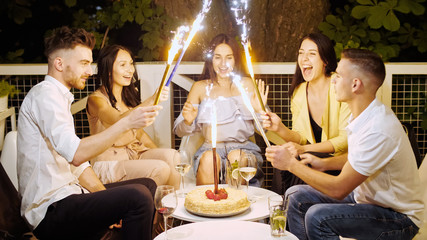Young cheerful people sitting in cafe at night with firework sparklers.