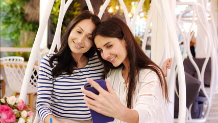 Two pretty girls are laughing during look over photos on phone sitting at cafe