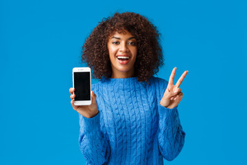 Carefree, cheerful african-american woman edit her photo with filter in app, showing result on smartphone display, make peace sign and smiling happily, standing blue background in winter sweater