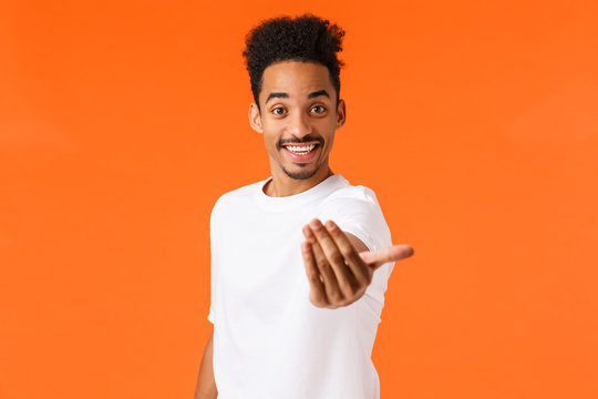 Come on join us. Happy and friendly outgoing african-american modern male student inviting participate, hiring, make come here gesture and smiling, lure, standing orange background