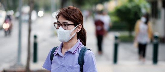 young Asian woman wearing protection mask against flu virus in the city. healthcare and air...