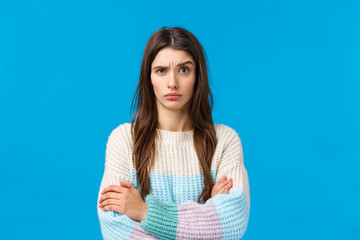 Skeptical, annoyed and displeased young woman hearing something stupid, nonsense, raise eyebrow suspicious and doubtful, cross hands over chest with disapproval, standing blue background