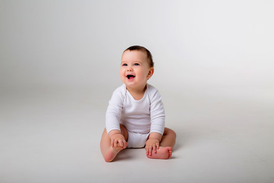 baby boy 9 months in a white bodysuit sitting on a white background, space for text