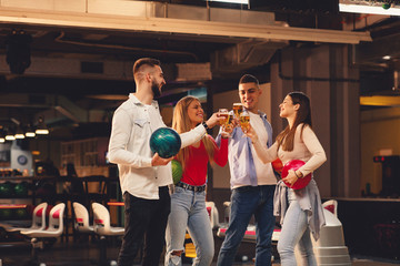 Group of friends toast with a beer in a bowling alley