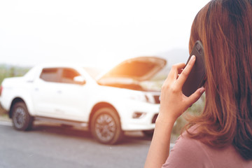 Young woman using mobile phone while looking at broken down car