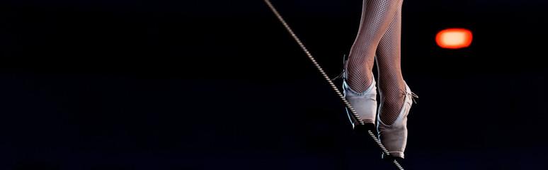 panoramic shot of aerial acrobat walking on tip toe on rope