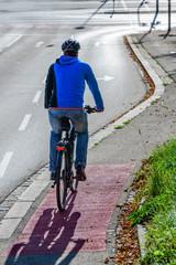Radfahrer wechselt auf einem Radweg von der Straße auf einen separaten Rad- und Fußweg