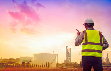 Engineering and petrochemical plants - Imagen, PPE conditions in oil and gas refineries, The young engineer stood in front of the oil refinery in the morning with beautiful light in the red radio.