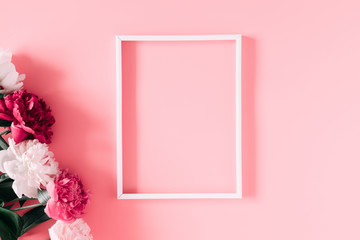 Beautiful flowers composition. Blank frame for text, pink and white peonies flowers on pastel pink background. Valentines Day, Easter, Birthday, Mother's day. Flat lay, top view, copy space