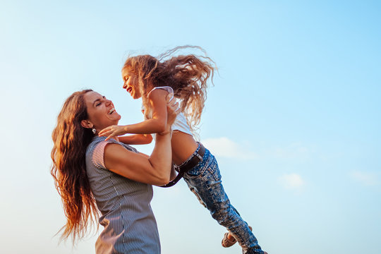 Woman playing and having fun with kid by summer river. Mother holding and spinning around daughter outdoors.
