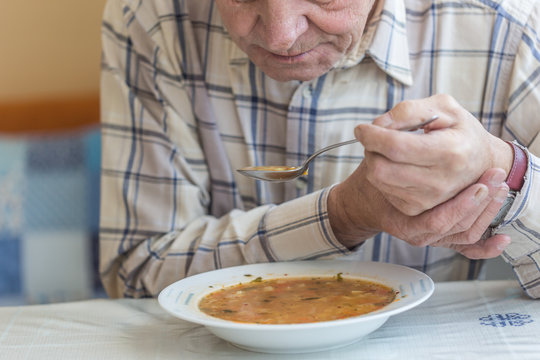 Elderly man with Parkinsons disease holds spoon in both hands