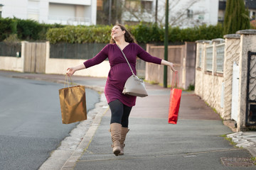 Active pregnant woman doing the household shopping