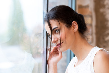 Portrait of a beautiful young woman standing at a window