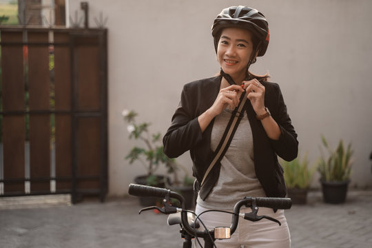 asian young woman wearing helmet bike for safety before go by bike to work