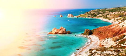 Seashore and pebble beach with wild coastline in Cyprus island, Greece by Petra tou Romiou sea rocks, panorama