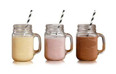 Banana, Strawberry and Chocolate milkshakes in Mason Jar glasses, with paper straws, isolated on a white backdrop