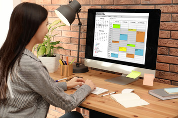 Young woman using calendar app on computer in office
