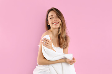 Young woman wiping body with towel on light pink background