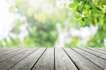 Wooden table and blurred green leaves in garden nature background.