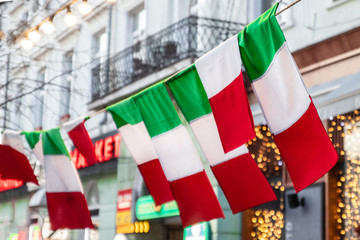 Flag of Italy hang on a city street. Tri-color flag fabric