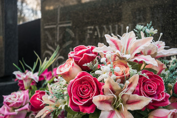 Family grave with artificial flowers and roses in the foreground and white frost