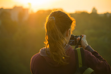 Silhouette of a girl taking pictures of sunrise