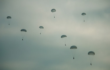 Army paratroopers jumping at air war action.
