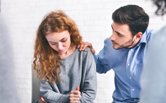 Caring husband comforting his depressed wife on meeting with marriage counsellor