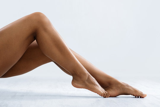 Attractive legs of african woman over grey background