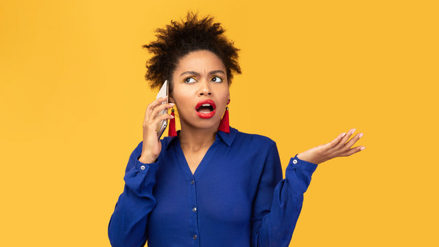 Upset young afro woman talking on mobile phone
