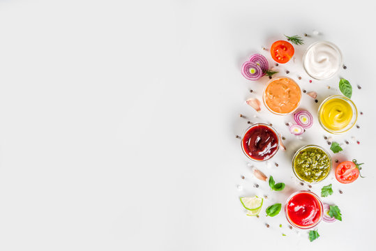 Set of sauces in small bowls - ketchup, mayonnaise, mustard, bbq sauce, pesto, classic burger sauce, with spices and herbs in. White background copy space top view