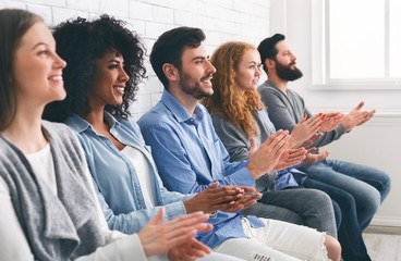 Multiethnic group of people applauding, clapping hands at meeting or seminar