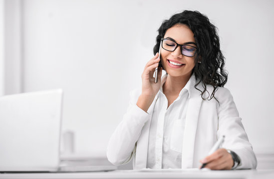 Latin businesswoman talking on phone and writing
