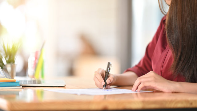 Side shot of woman red shirt while writing on the paper and sitting at the wooden working desk.
