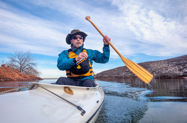 senior male is paddling expedition canoe