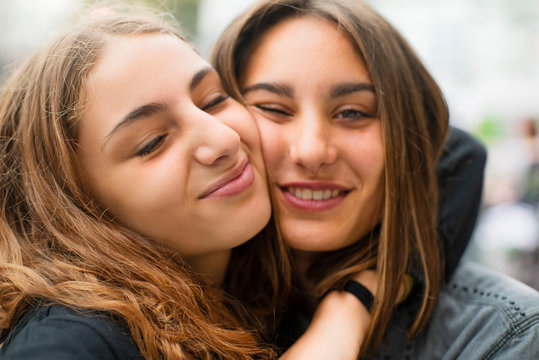 Portrait of smiling female friends embracing outdoors