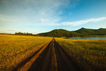 Dirt road passing through grassy landscape with mountains in background, Siberia, Russia