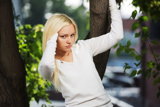 Young fashion blond woman in white long sleeve shirt