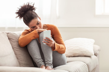 Depressed Afro Lady Holding Mobile Phone Sitting On Sofa Indoor