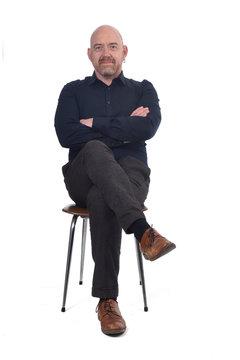 bald man sitting on white background